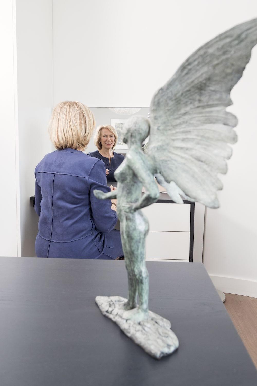Vrouw voor een spiegel met op de voorgrond een beeldje van een engel in de slaapkamer.