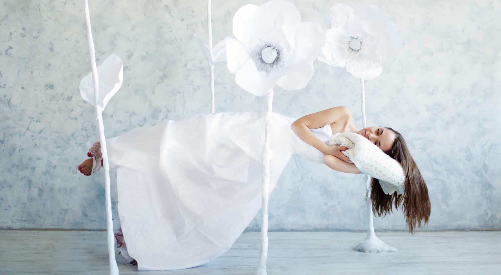 Een vrouw die slaapt met een grote witte jurk en witte bloemen om haar heen.