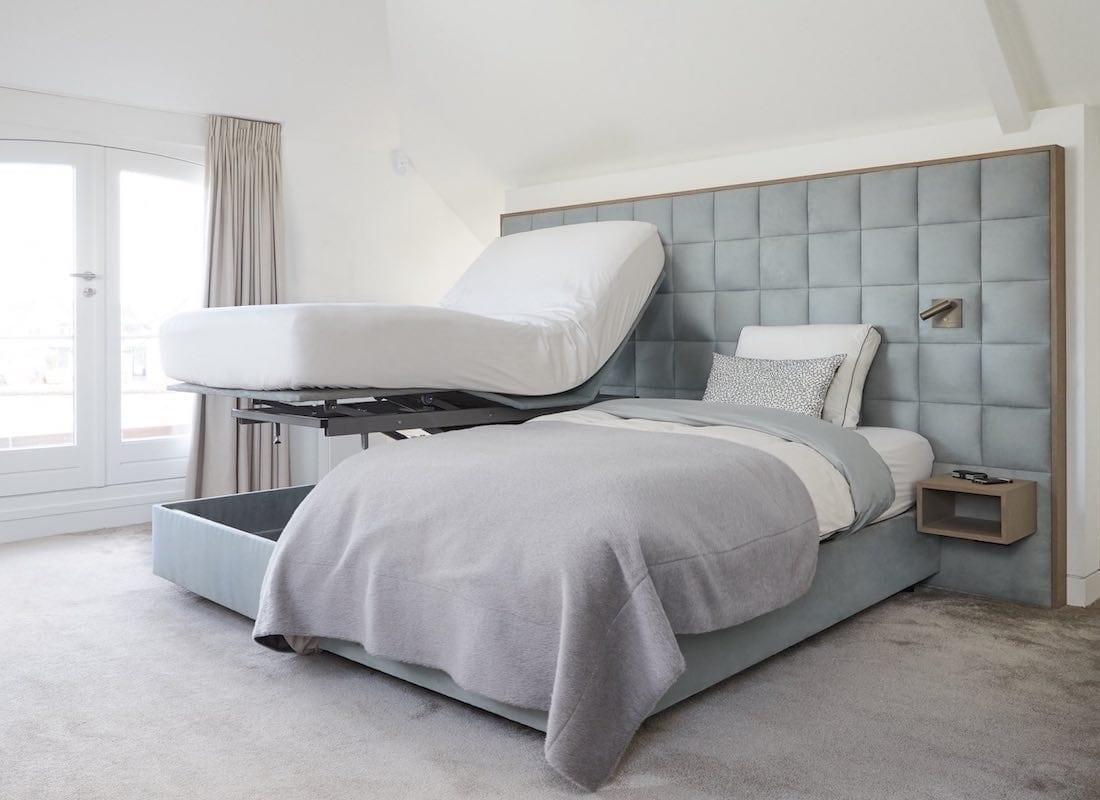 Een slaapkamer met een hoog laag boxspring waarvan een bed hoog staat en een bed laag.