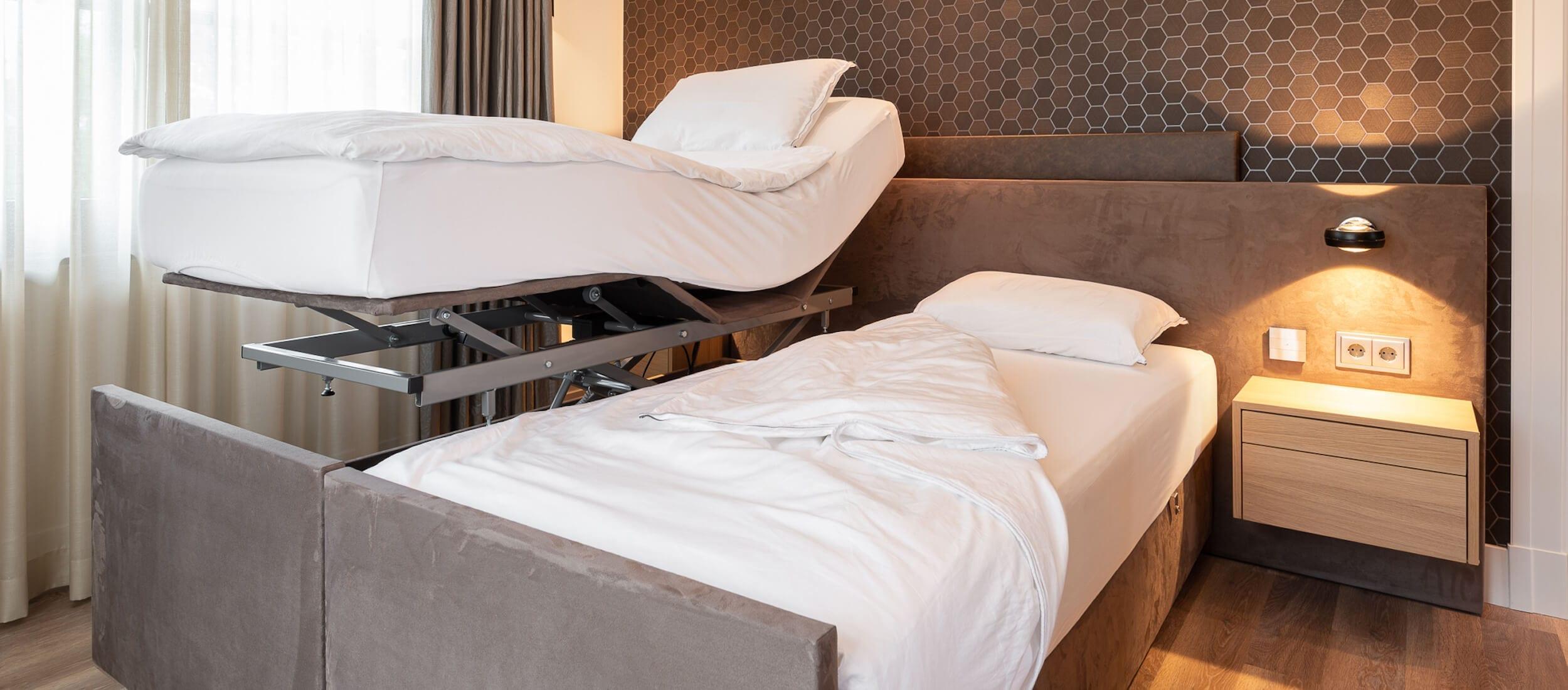 Hoog laag bed met ombouw in een slaapkamer met lamp aan.