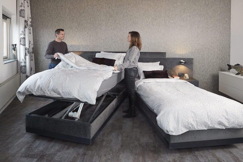 Hoog laag bed opmaken door een stel in de slaapkamer