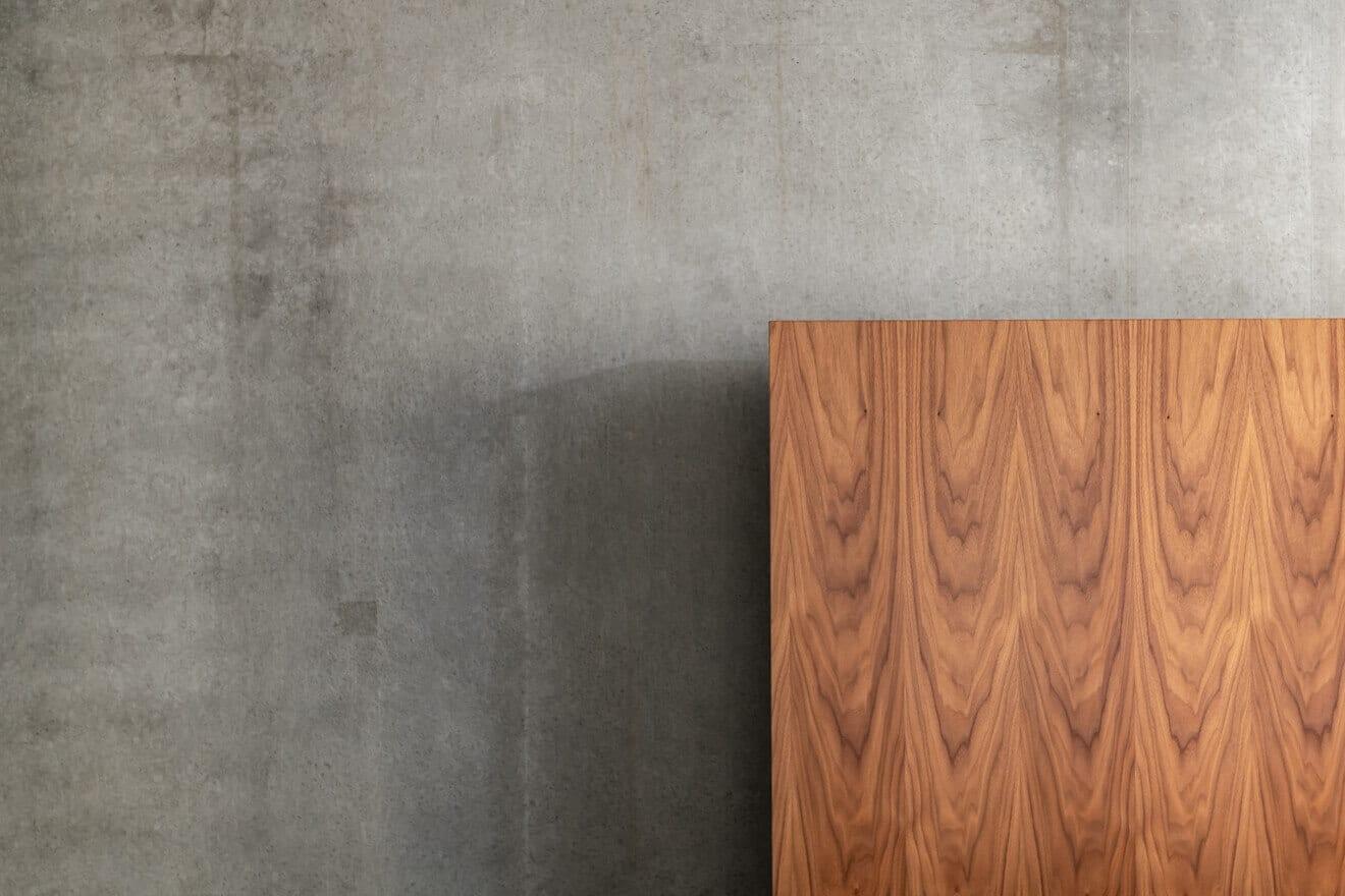 Wand slaapkamer van beton met hoofdpaneel van hout