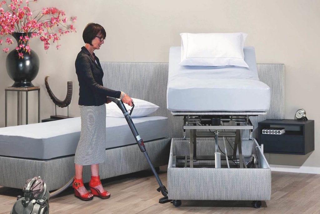 vrouw stofzuigt onder senioren hoog laag bed