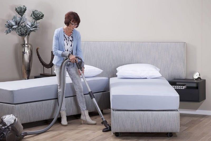 vrouw stofzuigt tussen deelbaar bed