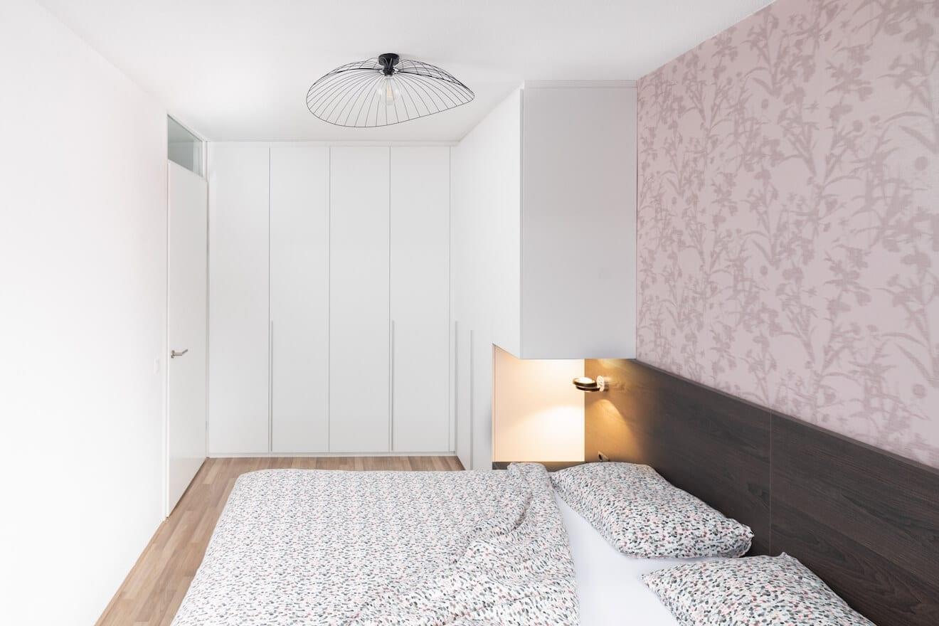 Kleine slaapkamer met houten bed en kastombouw