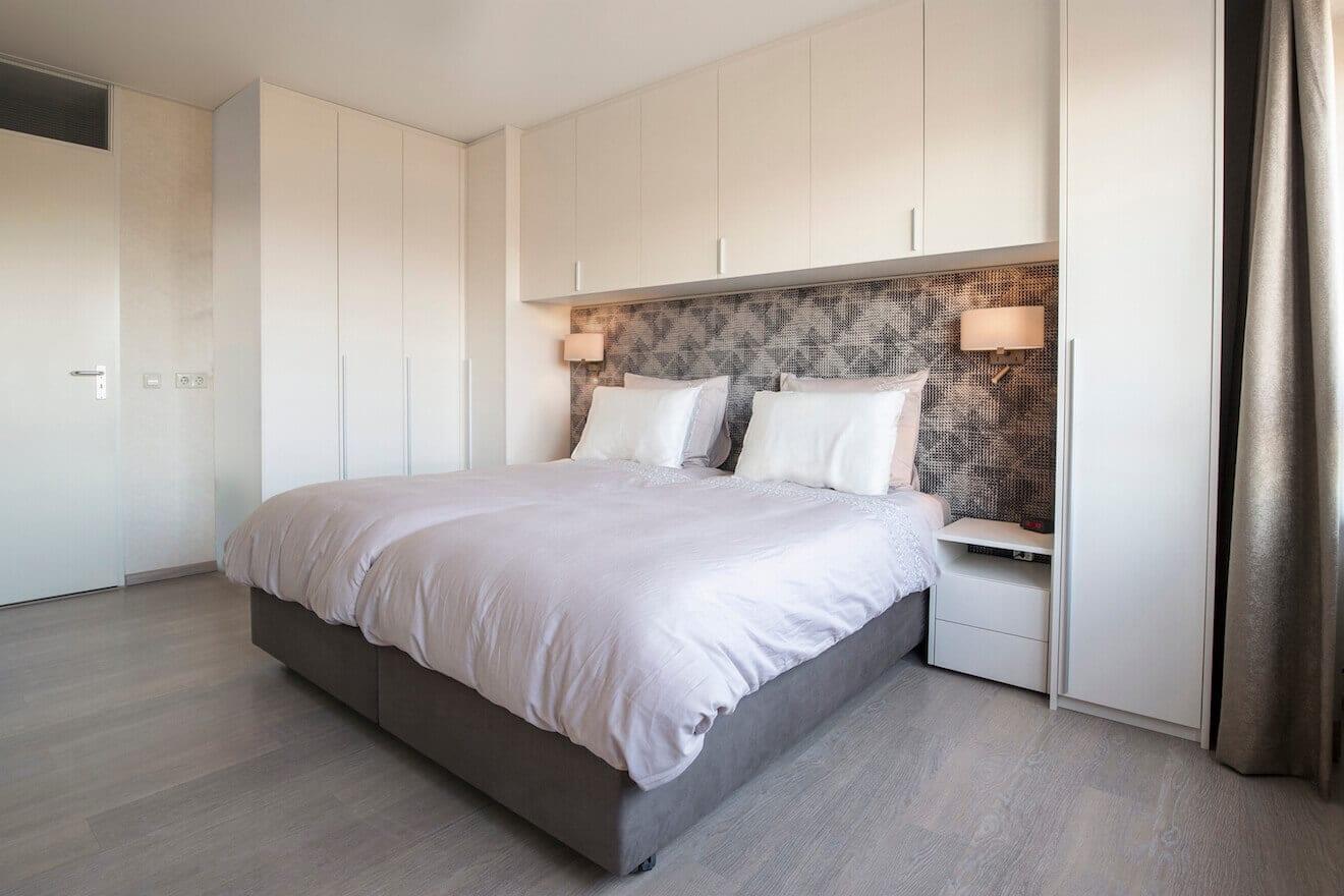 Luxe slaapkamer met hoog laag bed en kastombouw