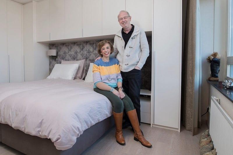 ouder stel bij bed en slaapkamerkasten