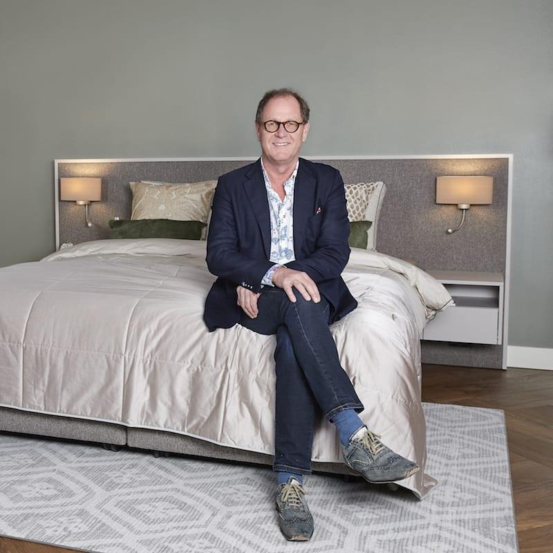 adviseur Wim Hofman zittend op bed