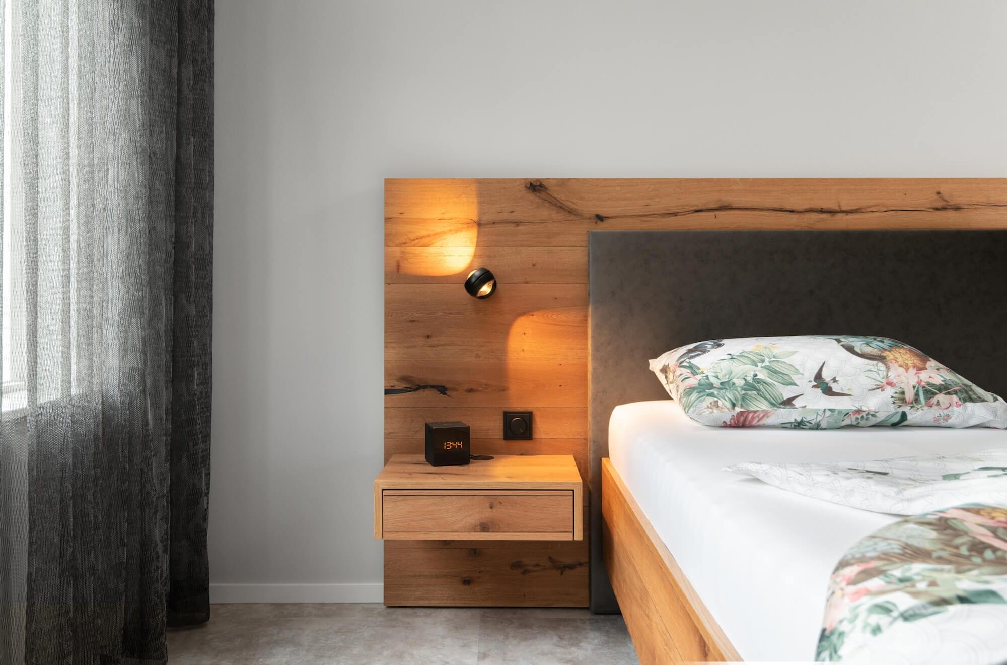 detail bed met zwevend nachtkastje en zwarte bedlamp nautilus