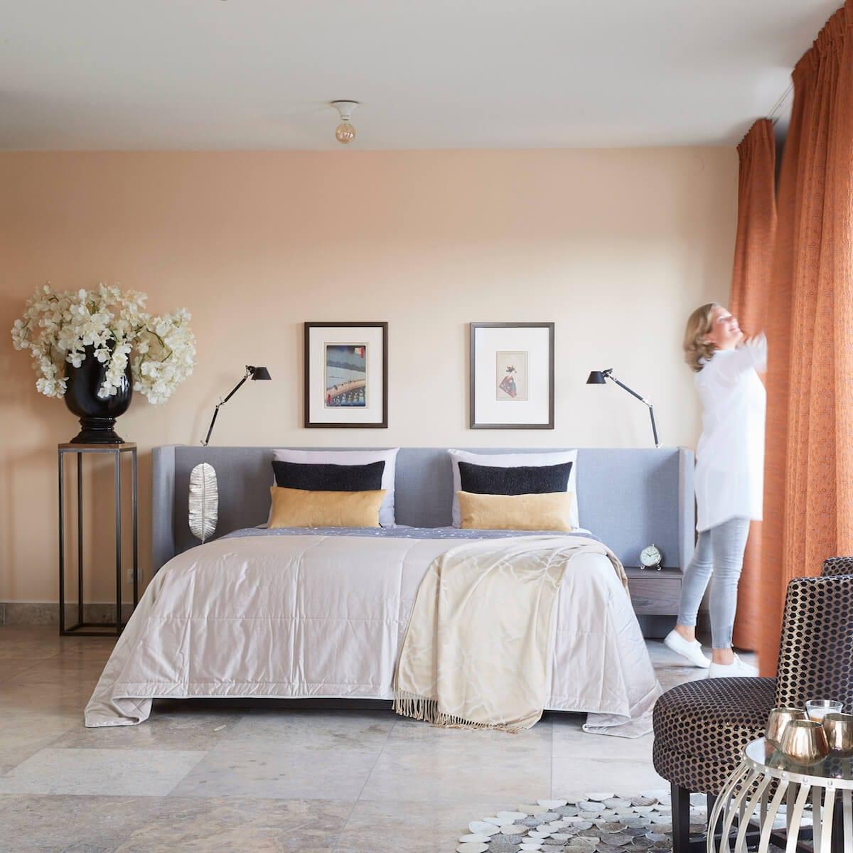 vrouw doet slaapkamergordijn open naast bed