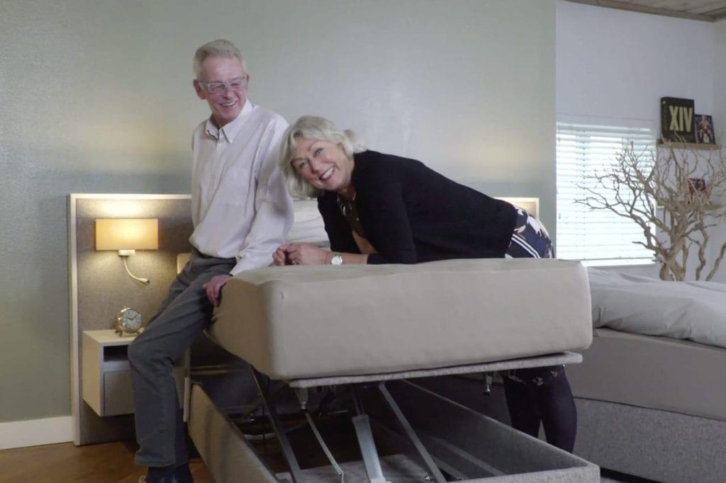 senioren stel zittend op hoog laag bed