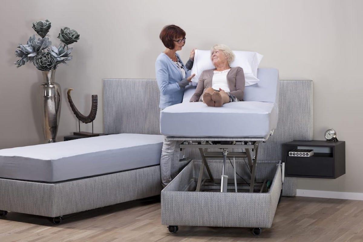 oudere dame in bed wordt geholpen door thuiszorg