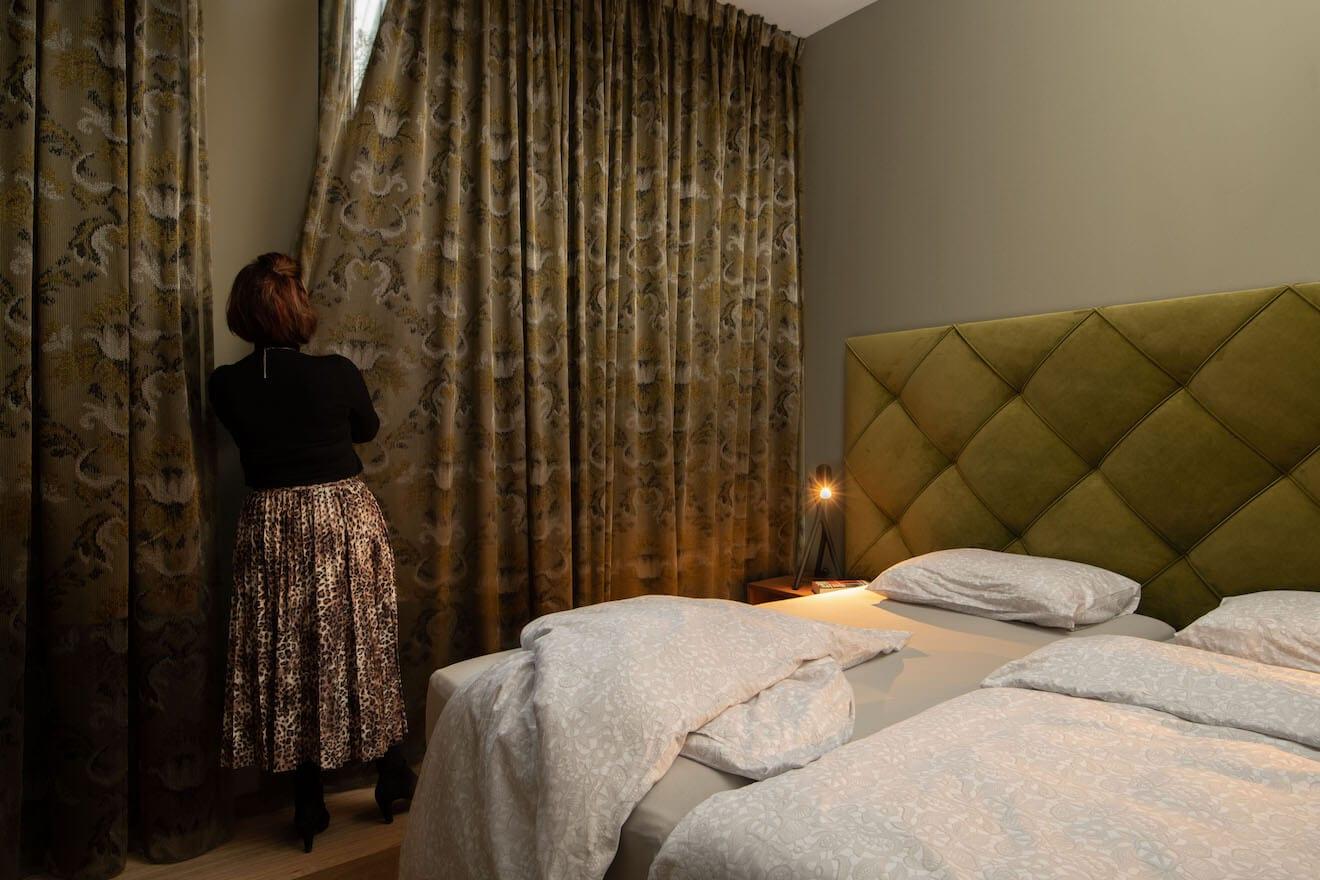 vrouw doet gordijnen dicht naast finotore bed