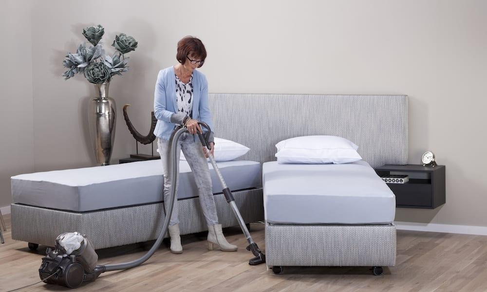 vrouw maakt schoon onder deelbaar bed
