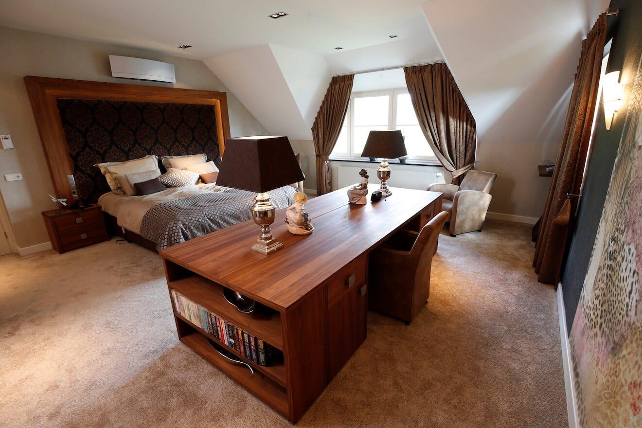 grote slaapkamer met ladekast met TV tegenover bed