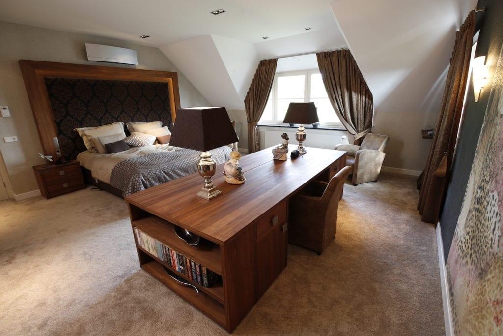 grote slaapkamer met bureau, ladekast en groot bed