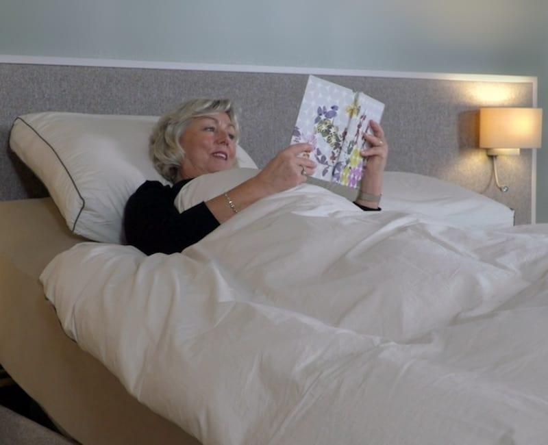 vrouw leest in elektrisch verstelbaar bed