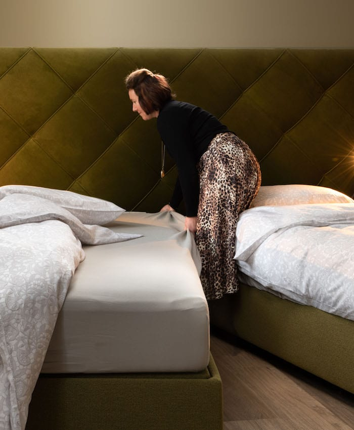 vrouw maakt hoog laag bed op