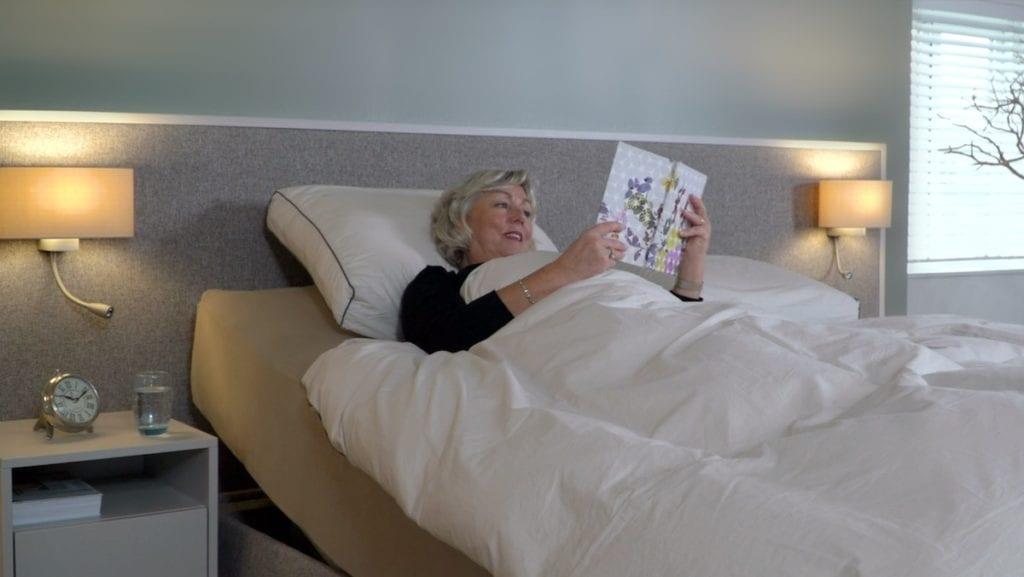 oudere vrouw leest boek in verstelbaar bed